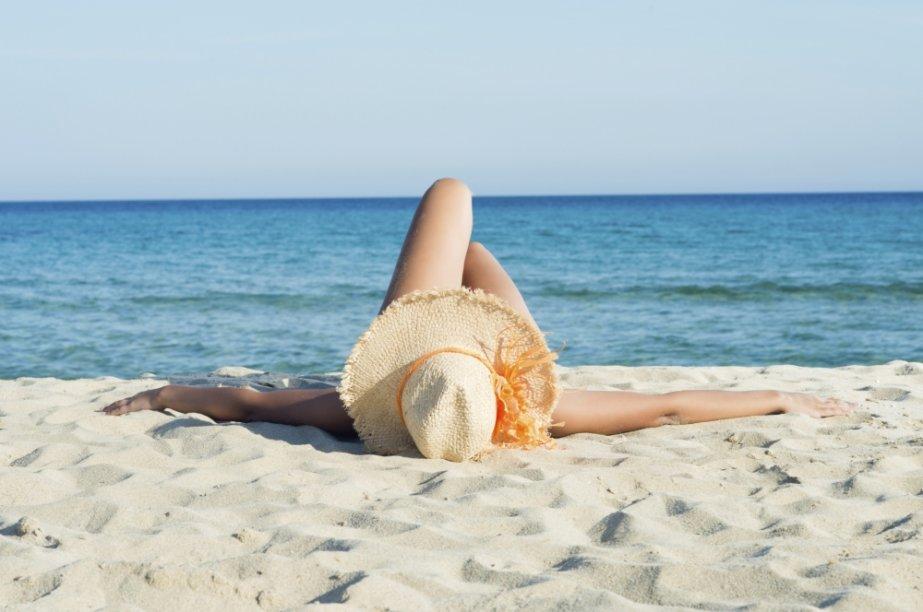 Mulher na praia tomando sol